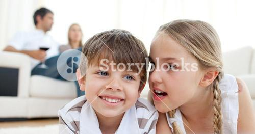 Little girl telling a secret to her brother