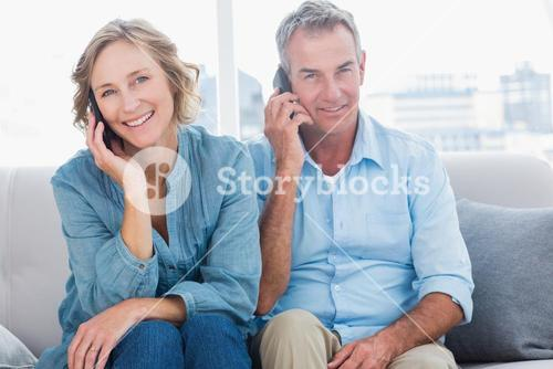 Cheerful couple on their mobile phones on the couch