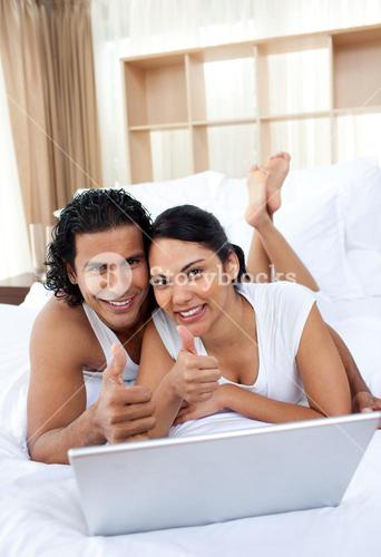 Couple with thumbs up using a laptop