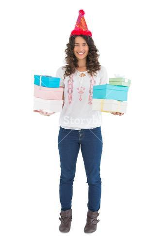 Smiling casual brunette wearing party hat holding presents