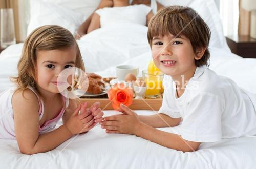Close up of cute brother and sister having breakfast with their parents