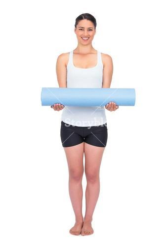 Cheerful slender model posing holding her rolled up mat
