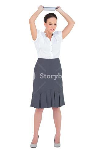 Angry businesswoman throwing her tablet pc