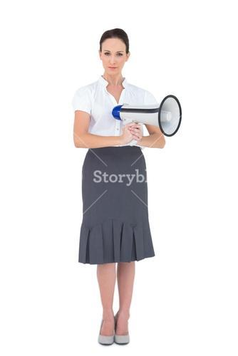 Unsmiling businesswoman holding megaphone