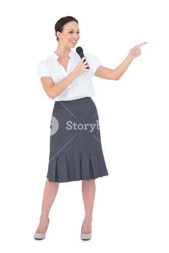 Attractive presenter holding microphone pointing