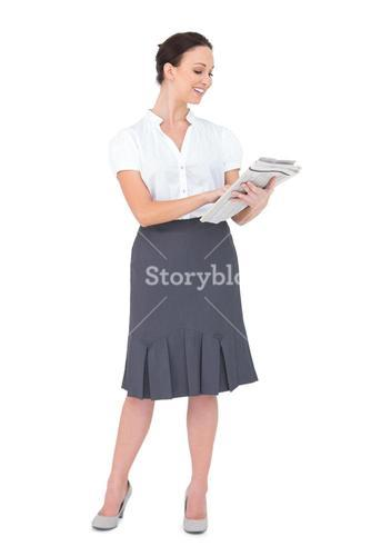 Smiling classy businesswoman holding newspaper