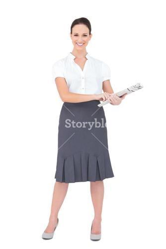 Cheerful classy businesswoman holding newspaper