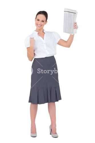 Victorious stylish businesswoman holding newspaper