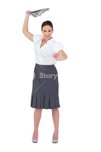 Angry stylish businesswoman throwing newspaper away