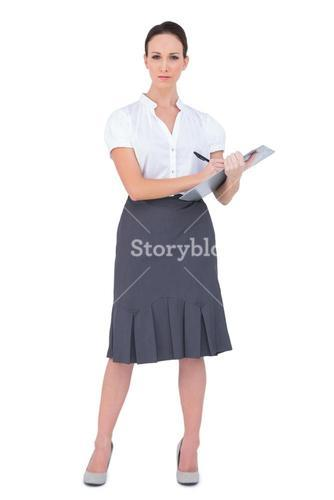 Unsmiling businesswoman holding clipboard