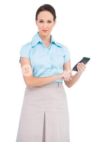 Serious classy businesswoman using calculator
