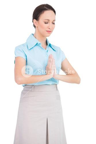 Peaceful young businesswoman praying
