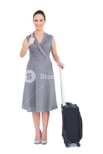 Cheerful gorgeous woman with her suitcase giving thumbs up