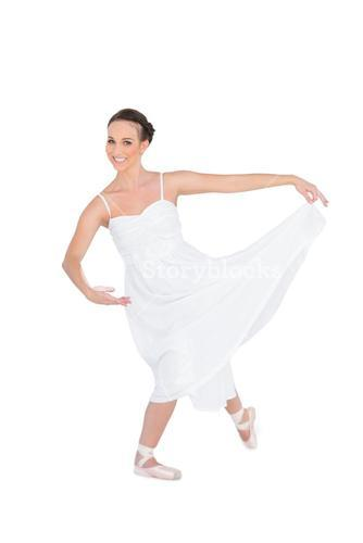 Happy young ballet dancer posing with leg back