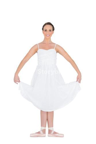 Cheerful young ballet dancer standing in a pose