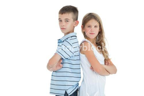 Serious young brother and sister posing back-to-back
