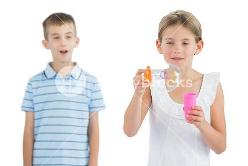 Girl making bubbles while her brother looking at her