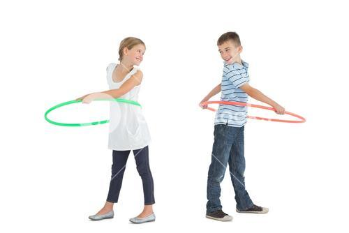 Smiling brother and sister playing with hula hoop