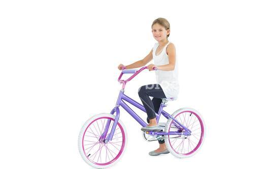 Smiling cute young girl riding bike