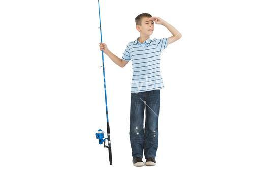 Young boy holding fishing rod looking away