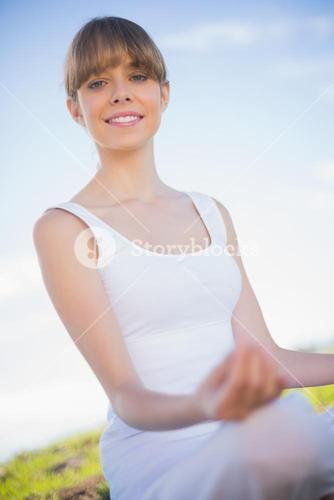 Smiling young woman relaxing in yoga position