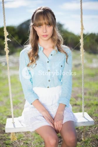 Angelic natural young woman sitting on swing