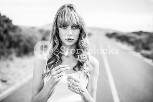 Black and white photograph of natural blonde holding flower