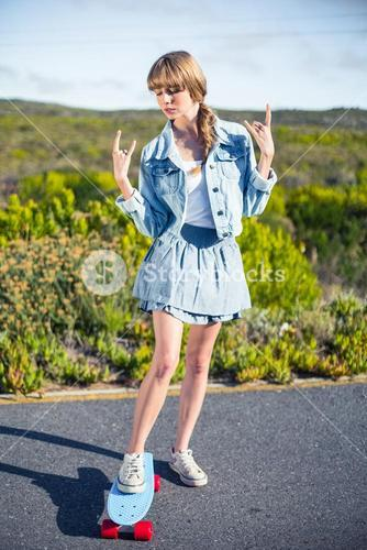 Attractive blonde making rock and roll hand gesture