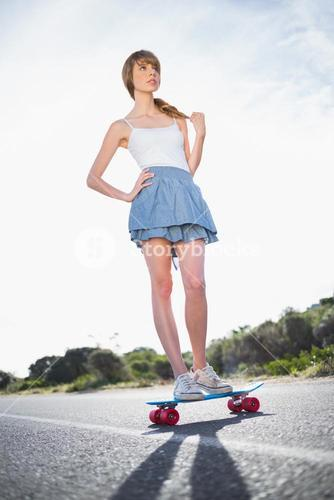 Cool skater girl doing standing on her skateboard
