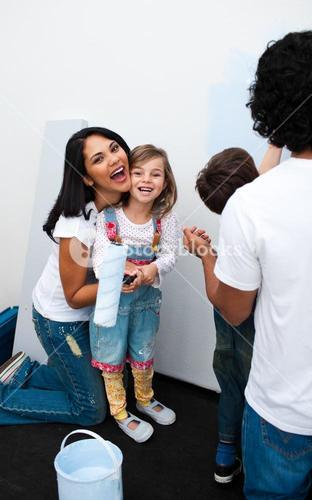 Happy parents with their children painting a room