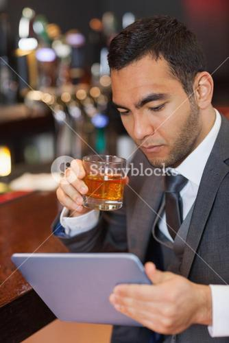 Serious businessman working on his tablet computer while having a whisky