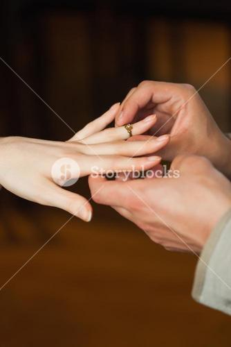 Close up on man putting on ring on his fiances finger during marriage proposal