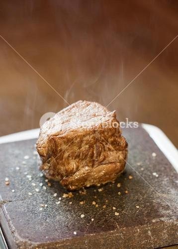 Steak sizzling on hot stone plate