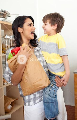 Cute Little boy unpacking grocery bag with his mother