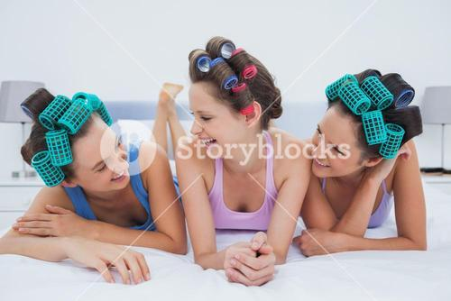 Laughing friends lying in bed