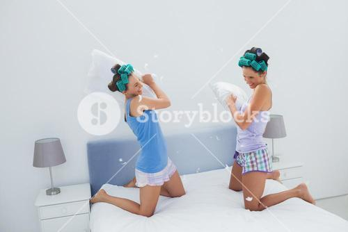 Girls in hair rollers having pillow fight
