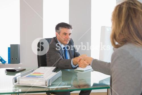 Serious businessman shaking the hand of interviewee