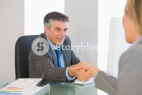 Pleased businessman shaking the hand of a interviewee