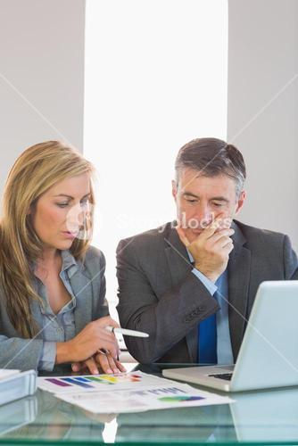 Two thoughtful businesspeople trying to understand figures