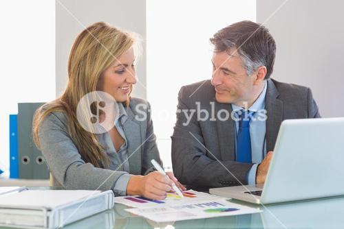 Two happy business people smiling to each other trying to understand figures