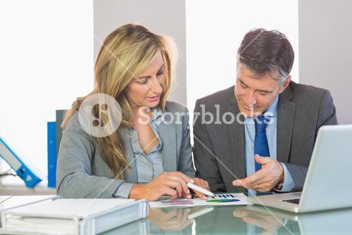 Two content business people trying to understand figures