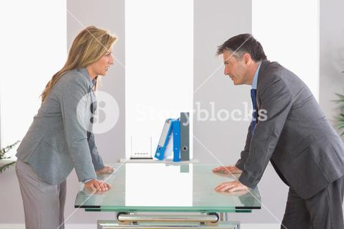 Two irritated businesspeople arguing on each side of a desk