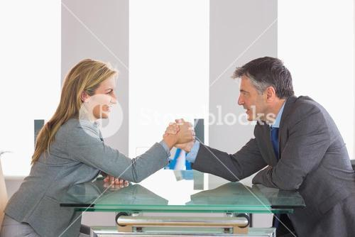 Two businesspeople having a showdown sitting around a table