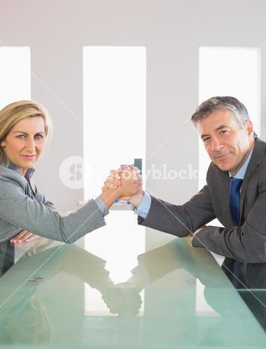 Two smiling businesspeople having a showdown sitting around a table