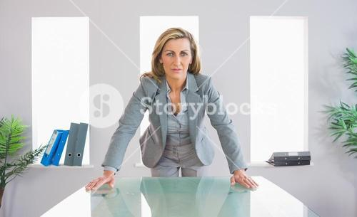 Serious businesswoman standing in front of desk