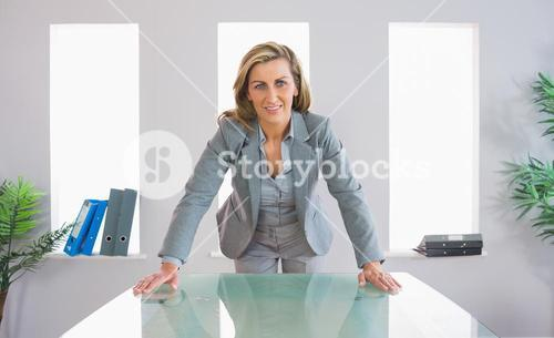 Pleased businesswoman standing in front of a desk