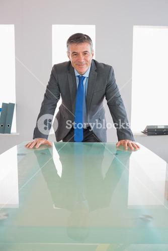 Laughing businessman standing in front of desk