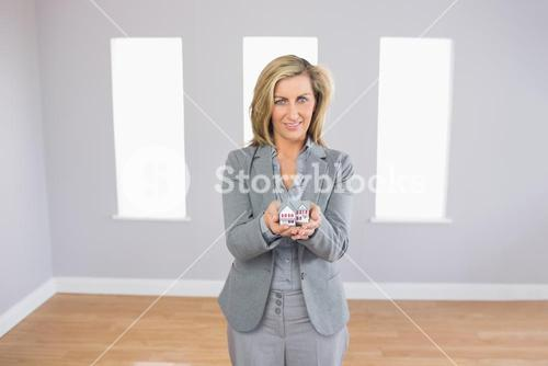 Cheerful realtor standing in a room presenting a mini model house