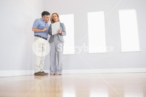 Concentrated blonde realtor showing a room and some documents to a potential attentive buyer