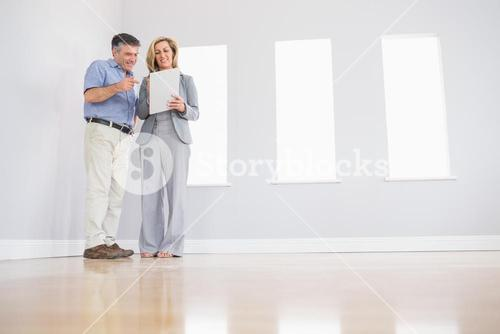 Cheerful blonde realtor showing a room and some documents to a potential attentive buyer